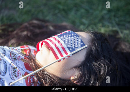 New York City, United States. 17th Apr, 2016. Young Sanders supporter lays supine with US flag over her face. Democratic - Stock Photo