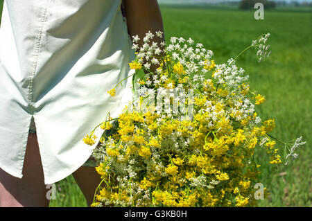 Girl with a bouquet of wild flowers seen from behind - Stock Photo