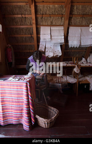 Woman demonstrating traditional wool spinning skills in a Madeiran triangular house. - Stock Photo