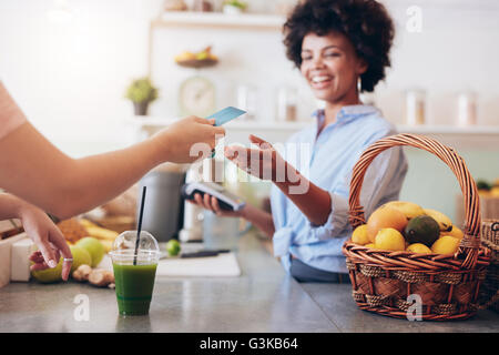 Shot of a female juice bar owner taking payment from customer. Female customer paying for juice with credit card. - Stock Photo