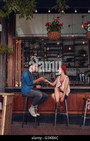 Full length shot of young couple sitting at cafe counter. Young man and woman sharing cigarette at coffee shop.