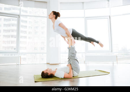 Beautiful young couple doing acro yoga in studio together - Stock Photo