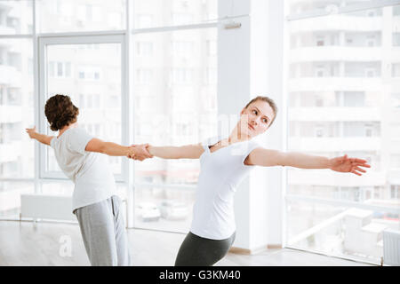 Beautiful young woman practicing yoga with partner in studio - Stock Photo