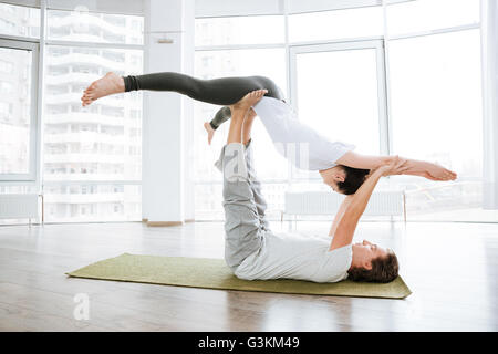 Peaceful young couple practicing acro yoga in studio together - Stock Photo