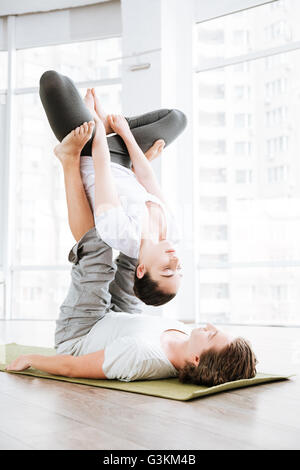 Young couple doing acro yoga exercises in studio together - Stock Photo