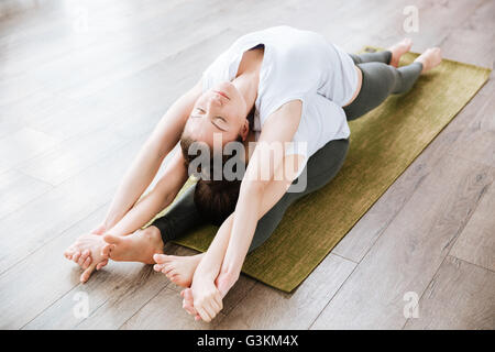Two relaxed young women stretching and practicing yoga in studio - Stock Photo