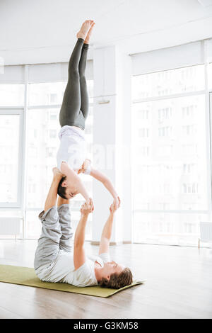 Peaceful young couple balancing and doing acro yoga in studio - Stock Photo