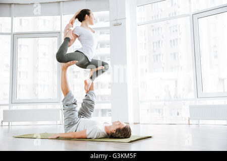 Concentrated young man and woman doing acro yoga for couples in studio - Stock Photo
