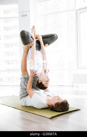 Young couple doing acro yoga in studio together - Stock Photo