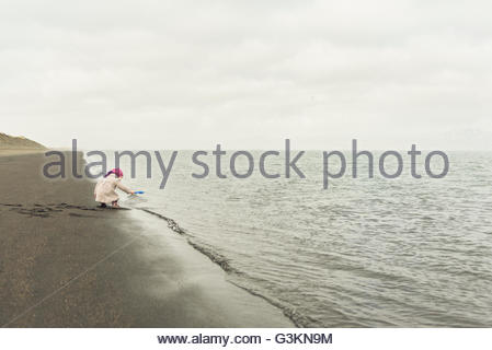 Young girl playing on beach at water's edge, Eyrarbakki, Iceland - Stock Photo