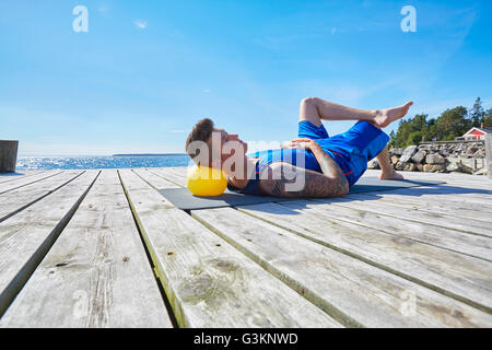 Tattooed man lying on pier using ball as pillow - Stock Photo