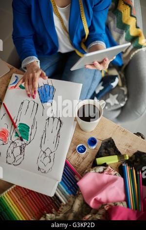 Overhead view of woman in design studio using digital tablet - Stock Photo