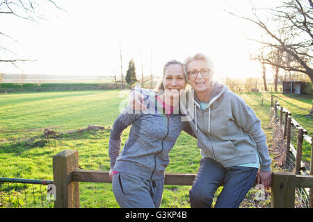 Women wearing sports clothing leaning against fence looking at camera hugging and smiling - Stock Photo