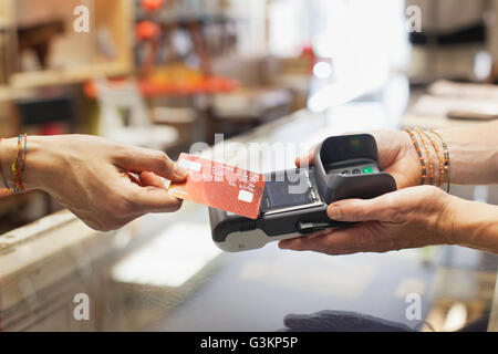 Cropped view of womens hand using credit card to make contactless payment on chip and pin machine - Stock Photo
