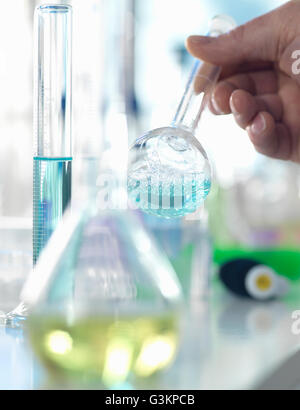 Scientist preparing a chemical formula in a conical flask during an experiment in the laboratory - Stock Photo