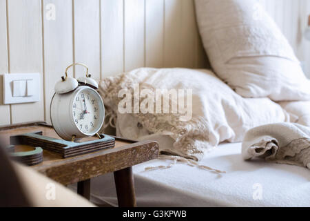 Unmade bed, alarm clock on bedside table - Stock Photo