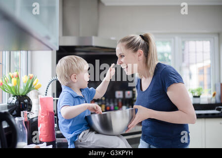 Mother and son fooling around whilst baking, son putting mixture on mother's nose - Stock Photo