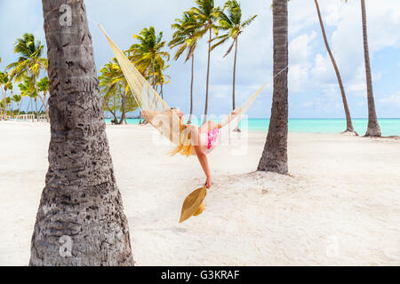 Young woman sunbathing in palm tree hammock at beach, Dominican Republic, The Caribbean - Stock Photo