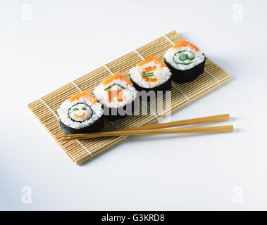 Salmon sushi on placemats with wooden chopsticks - Stock Photo