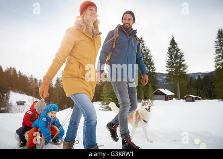 Parents pulling sons on toboggan in winter landscape, Elmau, Bavaria, Germany - Stock Photo