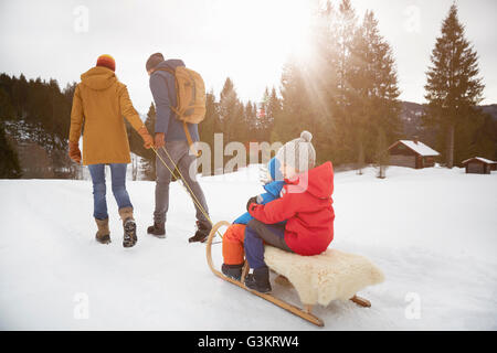 Rear view of parents pulling sons on toboggan in snow landscape, Elmau, Bavaria, Germany - Stock Photo