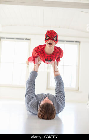 Father lying on floor holding up son wearing superhero costume - Stock Photo