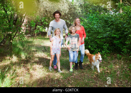 Family with dog walking together in forest - Stock Photo