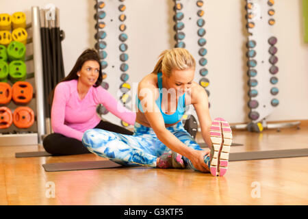 Women in gym sitting on yoga mat doing leg stretching exercises - Stock Photo
