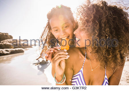 Girl and mother sharing ice lolly on beach, Cape Town, South Africa - Stock Photo
