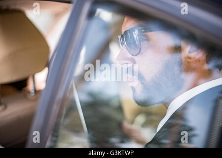 Young businessman wearing sunglasses looking out of car window from backseat, Dubai, United Arab Emirates - Stock Photo