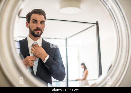 Mirror reflection of young businessman adjusting shirt and tie in hotel room, Dubai, United Arab Emirates - Stock Photo