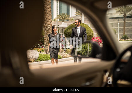 Car window view of businesswoman and man walking outside hotel, Dubai, United Arab Emirates - Stock Photo