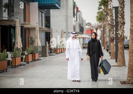 Middle eastern shopping couple  wearing traditional clothing carrying shopping bags, Dubai, United Arab Emirates - Stock Photo