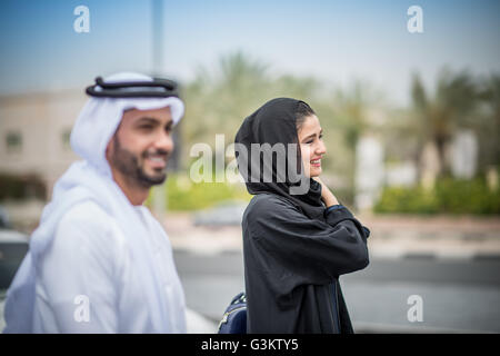 a3fa62b191265 ... Middle eastern couple wearing traditional clothing walking along street,  Dubai, United Arab Emirates -