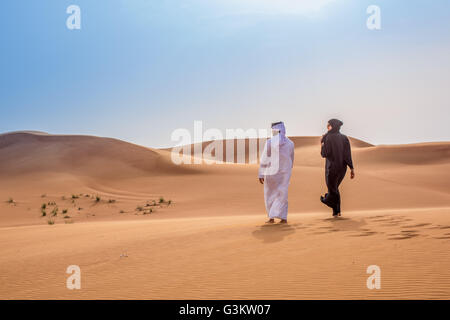 ae57bde7cb433 ... Couple wearing traditional middle eastern clothes walking in desert,  Dubai, United Arab Emirates -