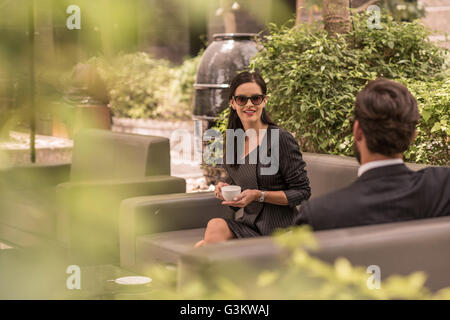 Businessman and woman talking on hotel garden sofa, Dubai, United Arab Emirates - Stock Photo