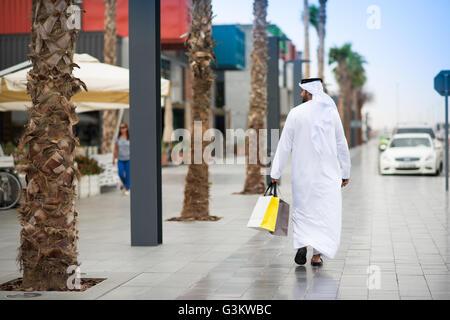 Rear view of man wearing dishdasha walking along street carrying shopping bags, Dubai, United Arab Emirates - Stock Photo
