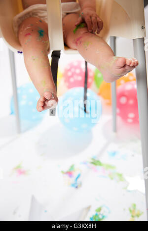 Baby's Legs Smeared with Food Dangling from High Chair - Stock Photo