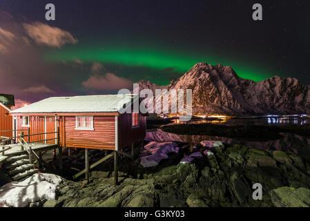 Northern lights or aurora borealis over Rorbuer fishing cottage, Svolvær, Austvågøy, Lofoten, Norway - Stock Photo