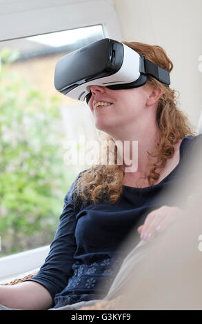 virtual reality headset worn by female person - Stock Photo