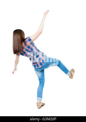 Back view woman Balances waving his arms. Standing young girl in jeans. Rear view people collection. backside view - Stock Photo