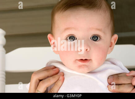 5-month old baby boy being held up by his mother - Stock Photo