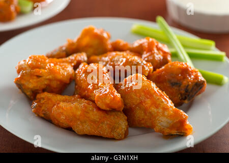 A plate of delicious spicy hot chicken wings with sriracha sauce and celery sticks. - Stock Photo