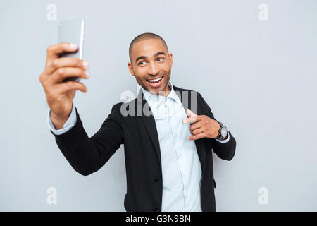 Young man making selfie photo on smartphone isolated on gray background - Stock Photo
