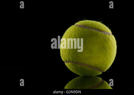 Single tennis ball isolated on black background - Stock Photo