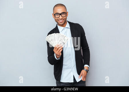 Cheerful african american young man standing and holding money - Stock Photo