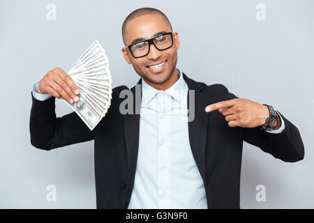 Happy african american young man holding dollars and pointing on it - Stock Photo