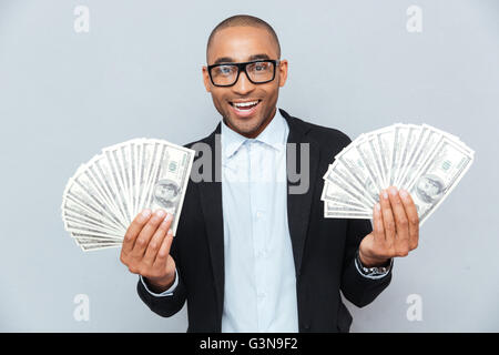 Smiling successful african young man holding a lot of money in both hands - Stock Photo