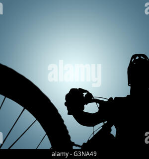 Composite image of man cycling with mountain bike - Stock Photo