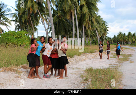 Local girls walking along the road in the evening, Christmas Island, Kiribati - Stock Photo